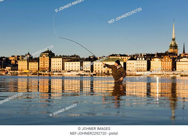 Man fishing in city