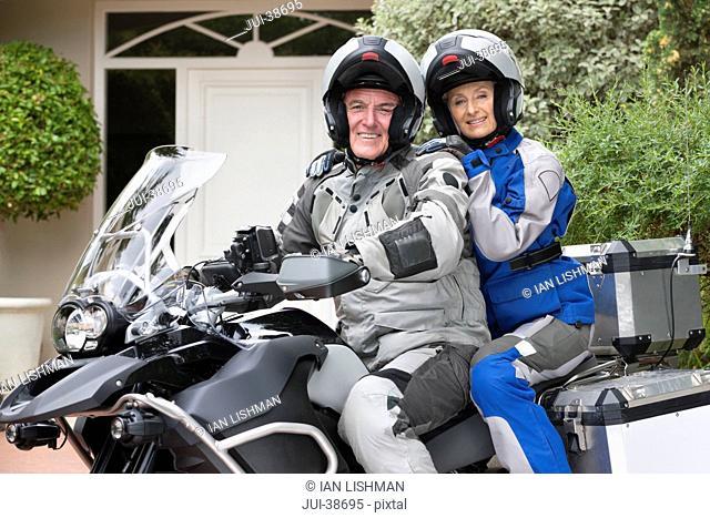 Portrait of happy senior couple wearing helmets on motorcycle in driveway