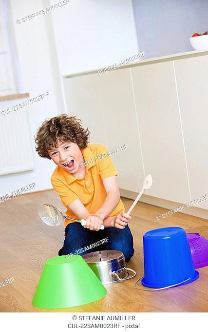 Boy playing drums on kitchen stuff