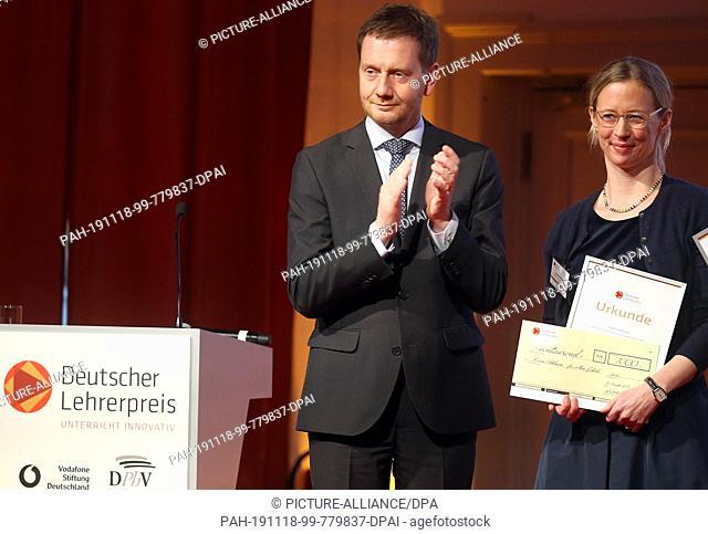 18 November 2019, Berlin: Michael Kretschmer (CDU), Minister President in Saxony, awards Karen Pohlman from the Protestant Gymnasium zum Grauen Kloster in...