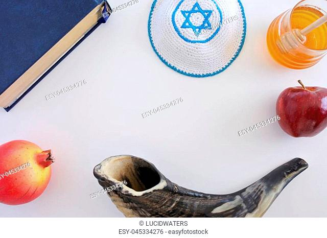 Flat lay view of Shofar, Torah book, Kippa, red apple , jar of honey and Pomegranate. Rosh Hashanah Jewish new year holiday concept. Copy space