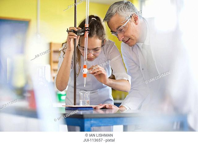Chemistry teacher helping high school student conducting scientific experiment
