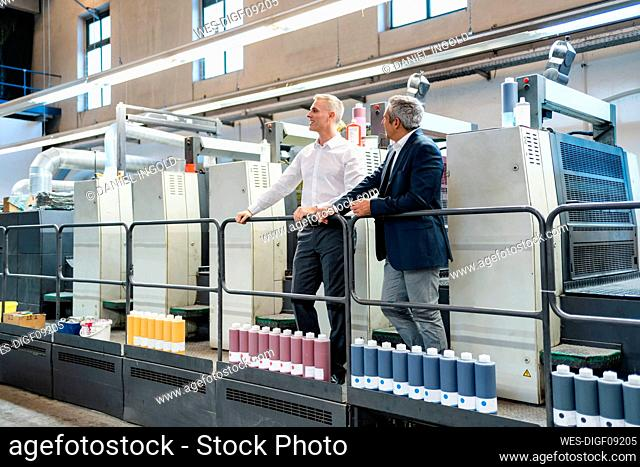 Two businessmen in a printing shop looking around