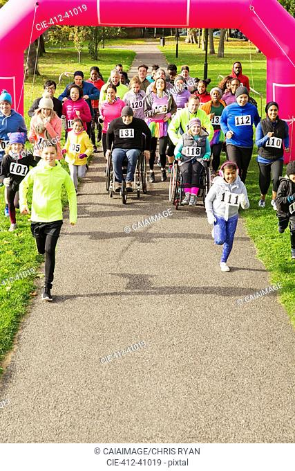 Runners starting at charity run in park