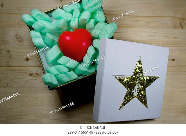 Red heart in christmas gift box with golden star on wooden background