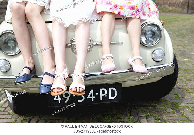 Helmond, Netherlands, 3 little girls with flowers all dressed up sitting on a vintage car