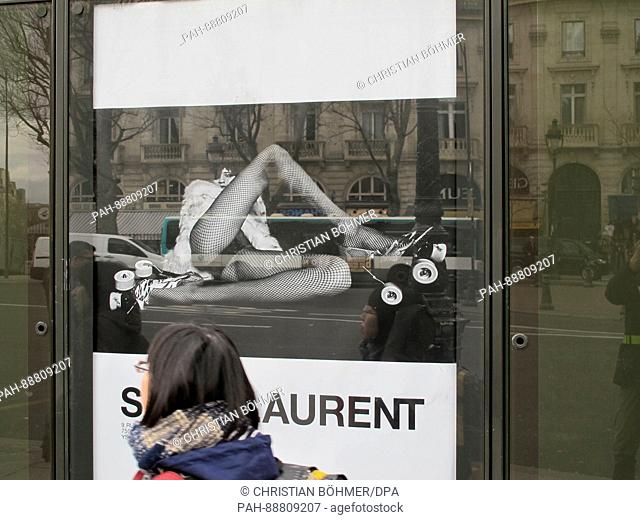 An advertisement poster of French luxury fashion brand Saint Laurent shows a woman with spread legs in fishnet stockings on Boulevard Saint-Michel in Paris