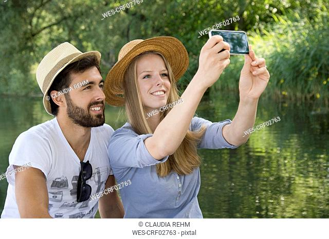 Smiling young couple at a lake taking a selfie