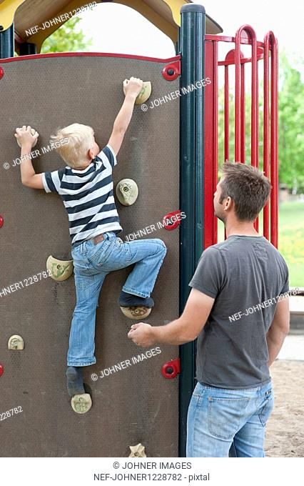Father climbing up Jungle Gym while father assisting