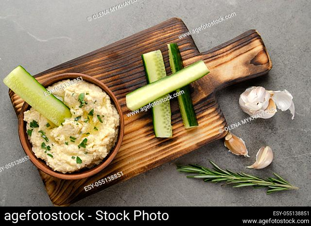 Flat lay view at vegetable Hummus dip dish topped with olive oil served with cucumber slices