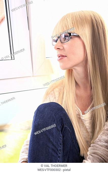 Portrait of a young woman wearing glasses looking out of window