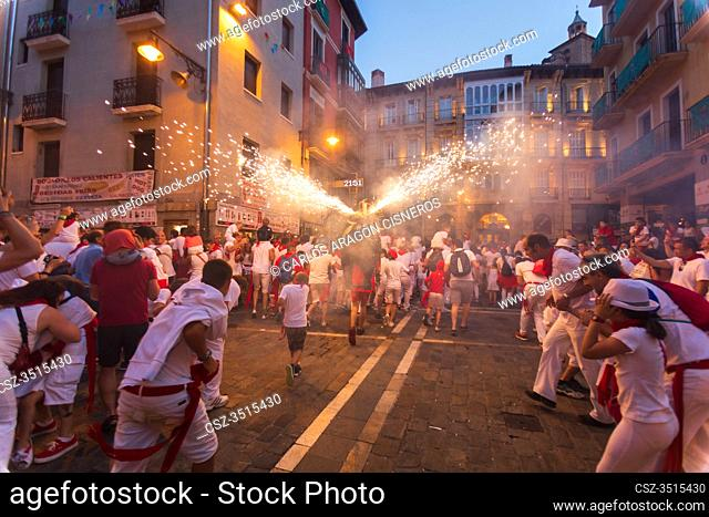 PAMPLONA, SPAIN - JULY 12, 2018: The youngest run with their parents in front of a fire bull at the San Fermin festivities