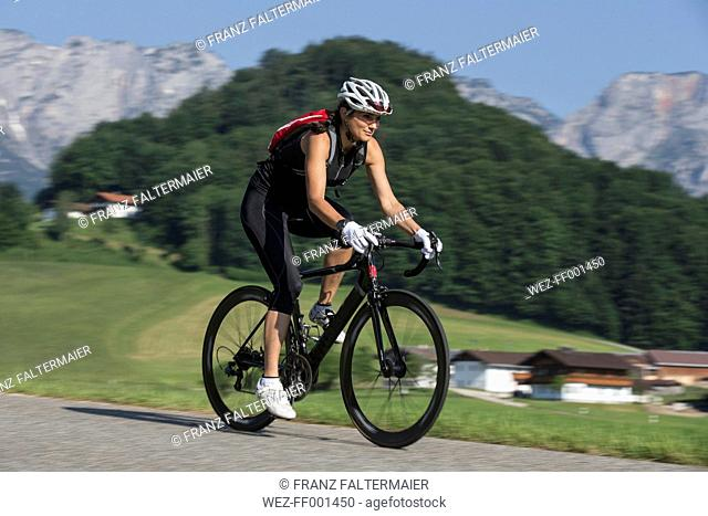 Germany, Marktschellenberg, sportive woman riding bicycle