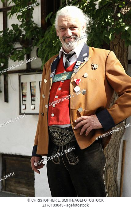 The Burgermesiter wearing traditional lederhosen heading to the Patronage day church service in Reith bei Seefeld, Austria