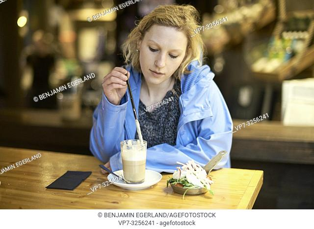 Young pondering woman stirring latte macchiato with drinking straw, in cafe, taking a break alone, thinking, in Munich, Germany