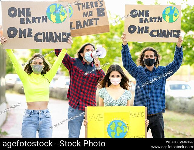 Men with women holding banner sign while protesting on climate change at footpath during pandemic