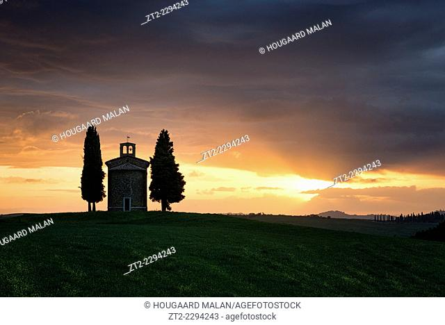 Landscape photo of an old Tuscany chapel against a dramatic sunset backdrop. Val D'Orcia, Tuscany, Italy