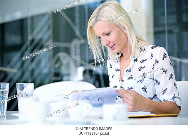 Businesswoman Sitting At Table In Office Reading Report