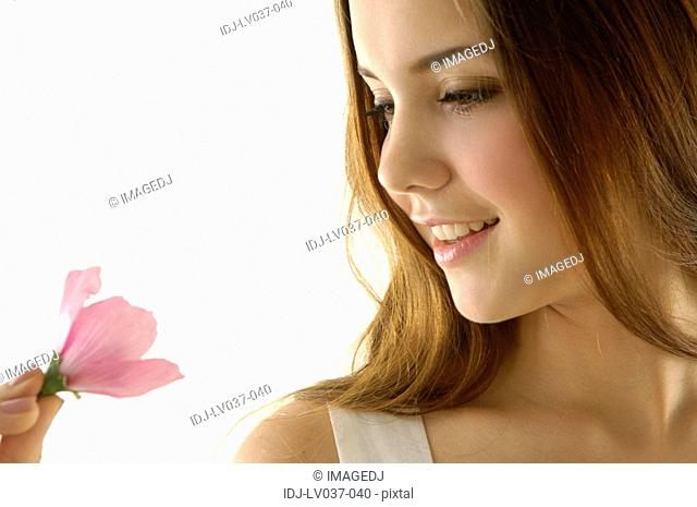 Close-up of a young woman smiling and holding a flower