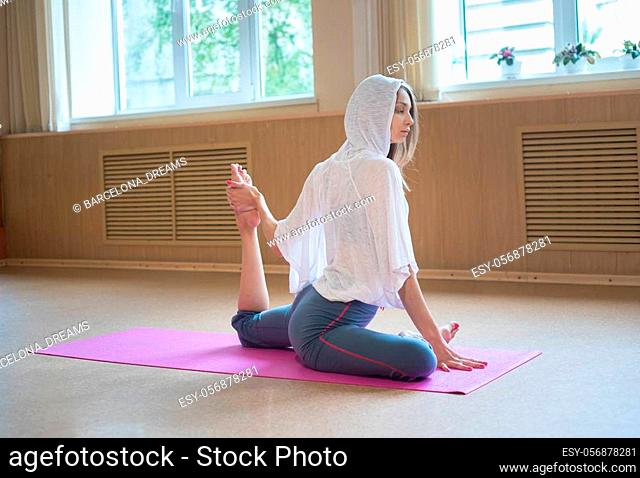 Young slim woman sitting on the yoga mat and doing stretching exercises - pulls the leg to the body. Mid shot