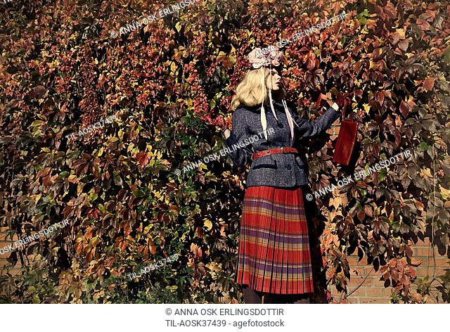 Lone female figure standing in garden by hedge