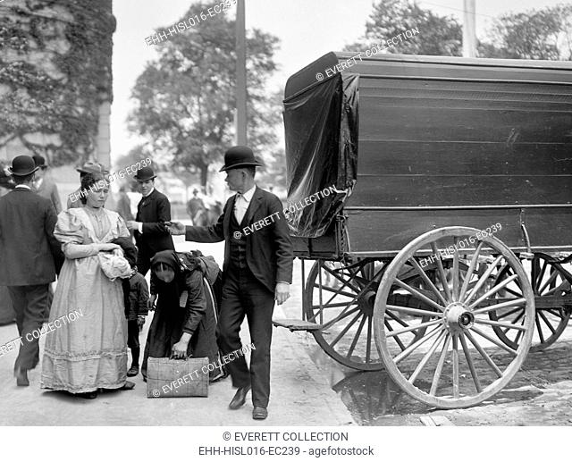 Two women immigrants and a child engage a wagon for transport to their next stop, probably a boarding house or railroad station