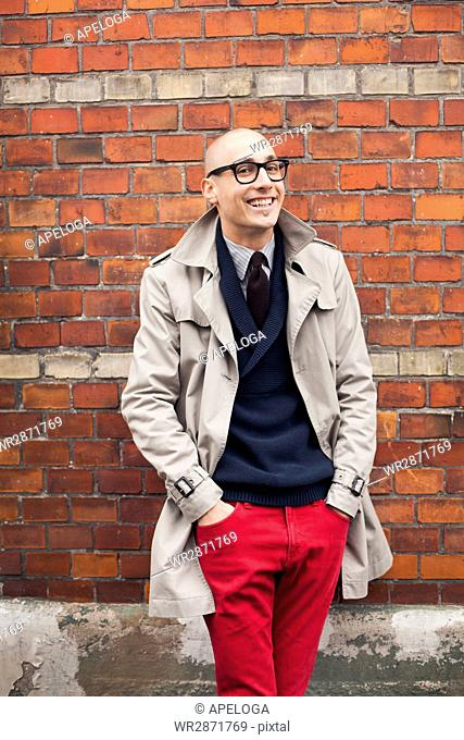 Portrait of smiling man standing with hands in pockets against brick wall