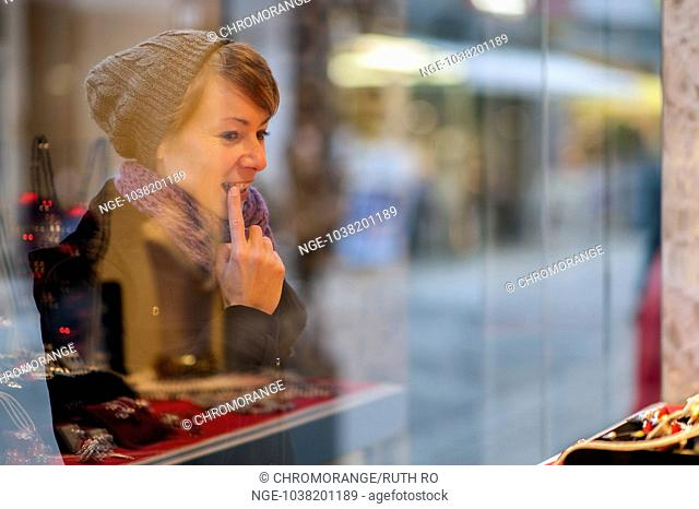 young woman considered the window of a jeweller s