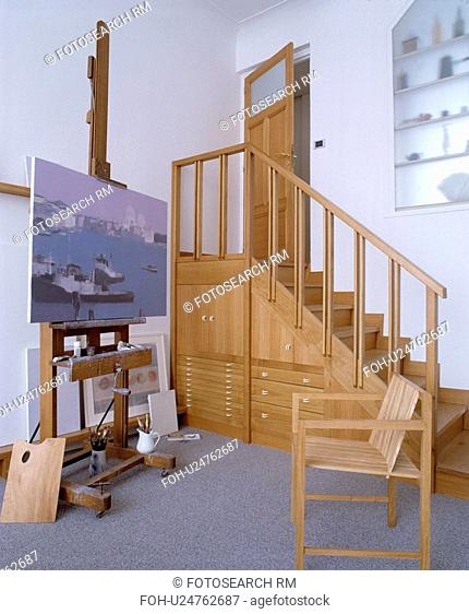 Wooden staircase with understairs storage cupboards and drawers in studio with easel and wooden chair