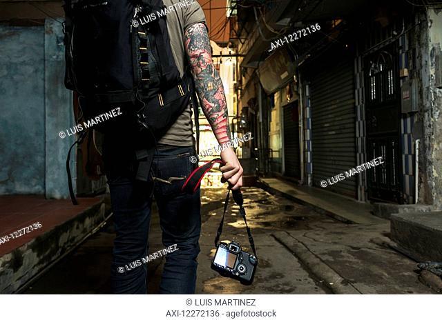 A male traveler carrying his camera down a narrow street; Xiamen, Fujian, China
