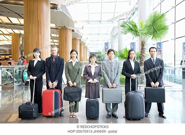 Business executives standing at an airport lounge with their luggage