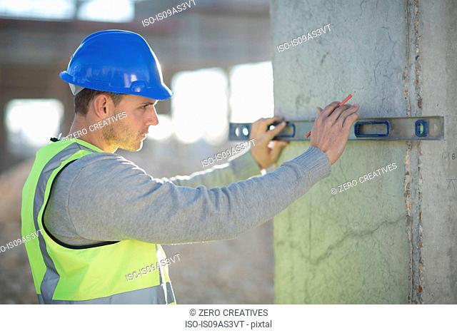 Surveyor using spirit level on construction site pillar