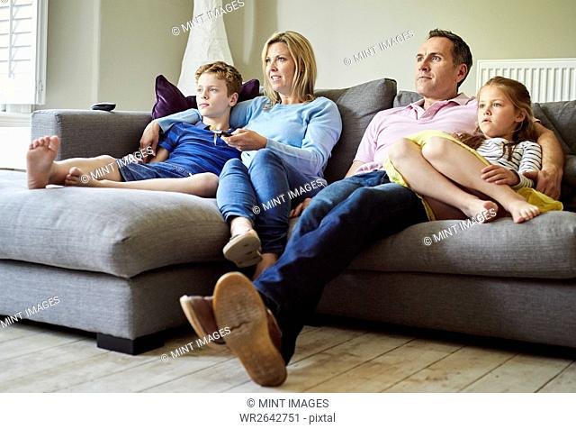 A family of four people, parents and a girl and boy, seated on the sofa together, watching television