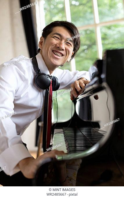 Young smiling man sitting at a grand piano in a rehearsal studio, wearing headphones round his neck