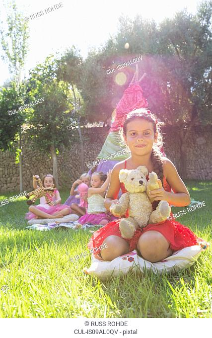 Portrait of girl holding teddy bear in front of teepee