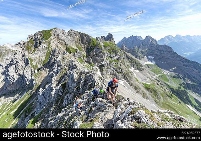 Mountaineer on a ridge on a secured via ferrata, Mittenwalder Höhenweg, view of mountain ridge, Karwendel Mountains, Mittenwald, Bavaria, Germany, Europe