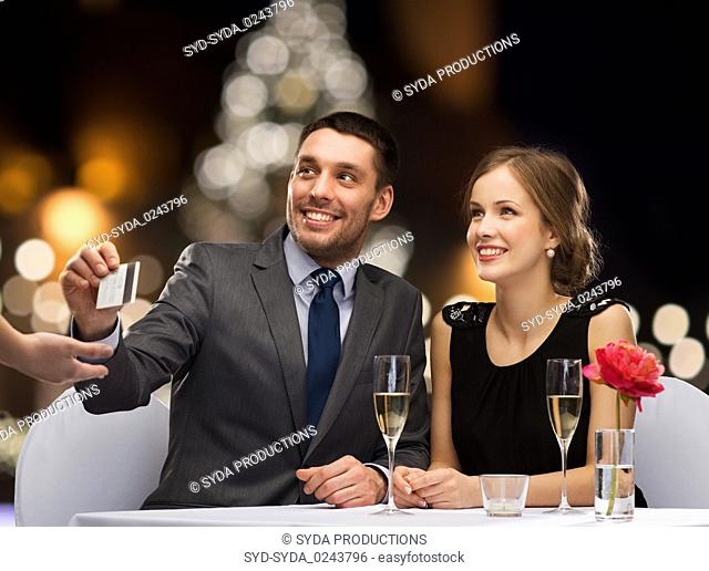 couple with credit card at christmas restaurant
