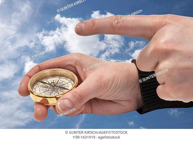 a compass is hand-held, a finger shows the direction