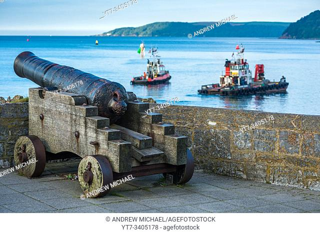 A restored 19th century Blomefield design cast iron cannon points across the water as boats passby, on Plymouth seafront in south Devon, UK