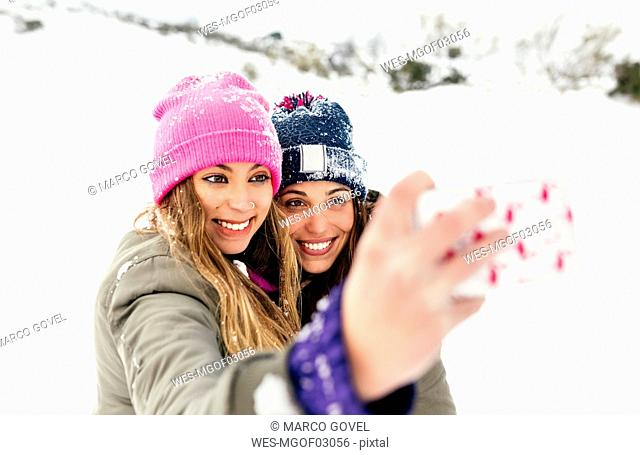 Two friends taking smart phone selfies in the snow