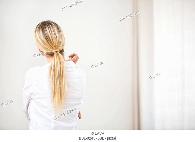 rear view of young woman looking at empty wall