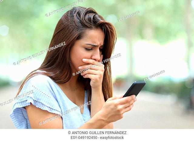 Sad girl complaining reading bad news on smart phone in the street
