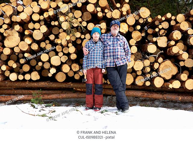Portrait of father and son, in front of stack of logs