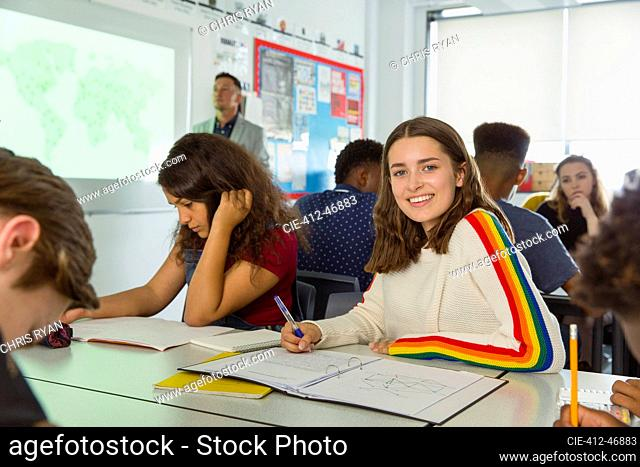 Portrait confident high school girl student taking notes during geography lesson in classroom
