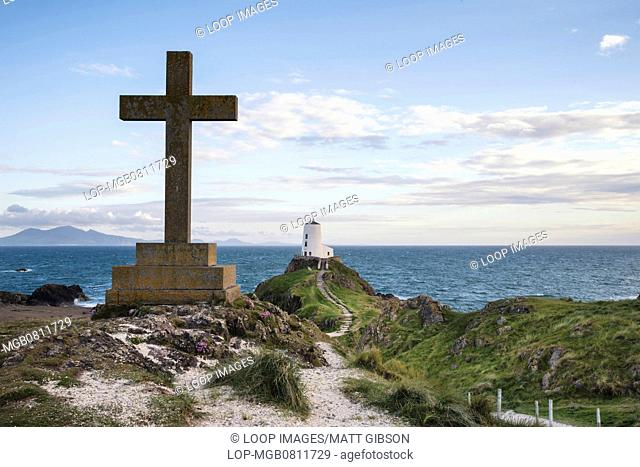 View of Cross monument on Ynys Llanddwyn Island in Angelsey with Twr Mawr lighthouse in background