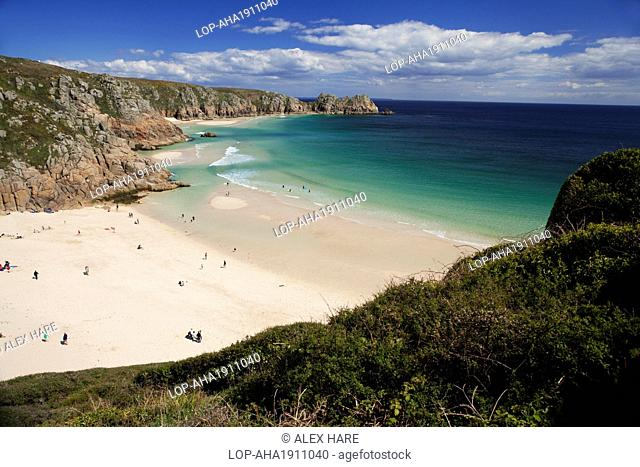 England, Cornwall, Porthcurno. People enjoying the sunshine on Porthcurno beach with Logan Rock in the distance. The beach and bay are regarded as one of the...