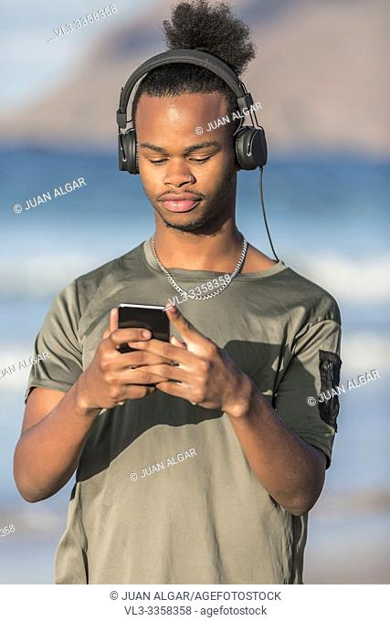 Handsome African American guy in modern headphones browsing smartphone and listening to music while standing on blurred background of sea