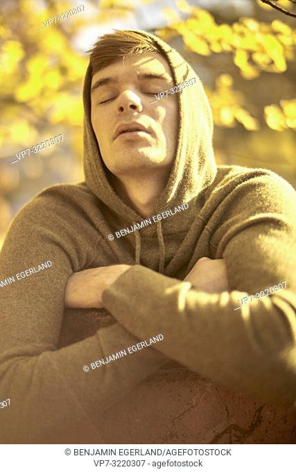 Young emotional man with closed eyes outdoors in autumn, wearing hoody pullover, in Munich, Germany