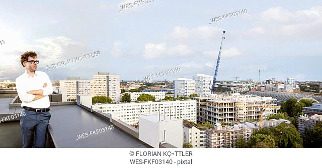 Germany, Berlin, businessman standing on roof terrace looking at view
