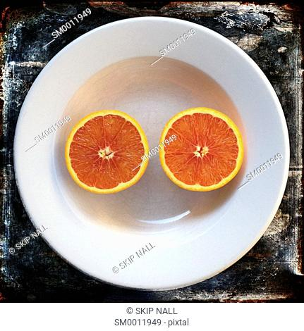 Two halves of an orange laying in a bowl